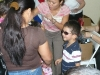 Dr. Betty Vo fitting eyeglasses on a child while mom watches